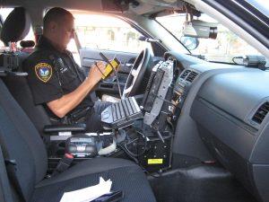 Policajt spisuje pokutu v aute